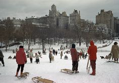 Sledders clamber up a snowy hill in a park lined with tall buildings.
